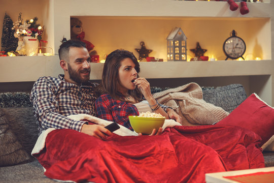 Couple eating pop corns while watching tv