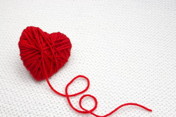 Red yarn ball like a heart on the white crochet background. Romantic Valentines Day concept. Red heart made of wool yarn with place for text, copyspace.