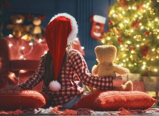Kid near Christmas tree.