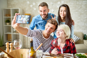 Portrait of four happy friends taking selfie at dinner table while celebrating holiday at home