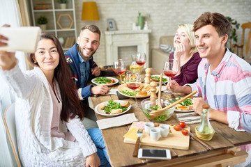 Portrait of happy friends taking selfie sitting at dinner table while celebrating festive occasion