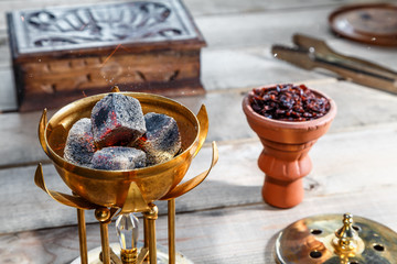 burning coals for Shisha Smoking are in the Golden bowl, made in the shape of a Lotus on the background of Smoking accessories