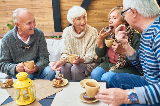 Group of elderly men and women warming themselves with hot tea and enjoying delicious cake while having gathering at cozy small patio
