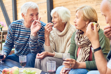 Group of aged friends spending pleasant time together at backyard party: they chatting animatedly with each other, drinking red wine and eating fresh fruits