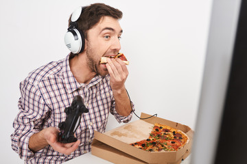 Unhealthy lifestyle. Close up of young beautiful funny bearded man with dark short hair playing online games with controller, talking with friends in headphones, eating pizza.