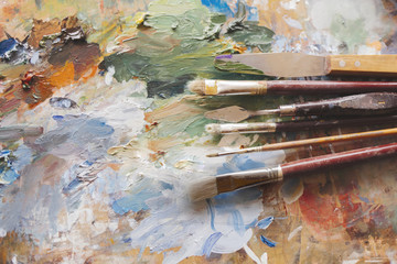 Dirty paint brushes. Artists brushes and oil paints on wooden palette.