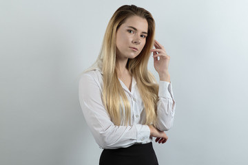 elegant young business lady posing for a portrait in a relaxed and friendly pose on a white background. Dressed in business style, long hair, white blouse and black skirt