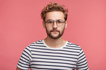 Portrait of hipster male in striped t shirt, wears round spectacles, has trendy hairstyle, looks confidently into camera, going to present lecture or conduct seminar for people, isolated on pink wall