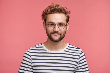 Indoor shot of pleasant looking bearded hipster guy wears spectacles and striped t shirt, looks directly into camera, isolated over pink studio background. Male student spends weekends at home alone