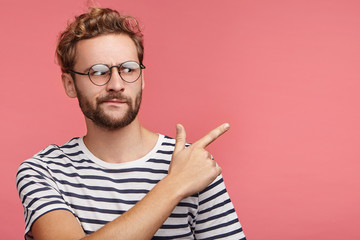 Displeased discontent bearded young man frowns face, indicates at copy space, wears round spectaces and striped t shirt. Puzzled hipster guy looks in bewilderment as sees something unexpected