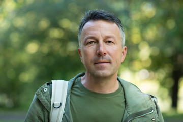 Handsome middle-aged man posing and looking at camera in autumn park over foliage. Outdoor male portrait. Male face close up.