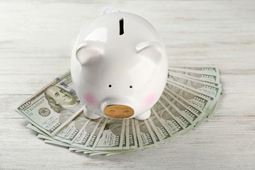 Cute piggy bank with money on wooden background
