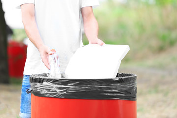 Young man throwing garbage into litter bin outdoors