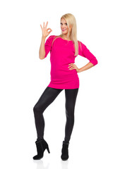 Beautiful Blond Woman Is Standing, Showing Ok Hand Sign And Smiling