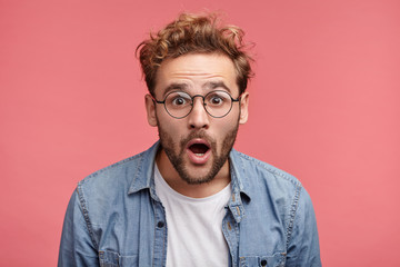 Stupefied attractive young bearded man looks with astonishment into camera, being amazed with negative news. Emotional hipster guy expresses surprisment, doesn`t believe his eyes. Facial expression 壁紙(ウォールミューラル)