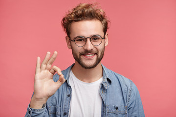 Positive hipster guy shows ok sign, demonstares that everything is fine, agrees with people who surrounds him. Confident cheerful man gestures indoors. Body language and human emotions concept