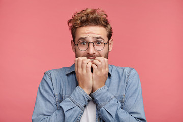 Worried hipster guy bites nails, looks nervous before passing exam or important event in his life. Embarrassed fashionable young man being afraid of difficulties, stands against pink background Wall mural