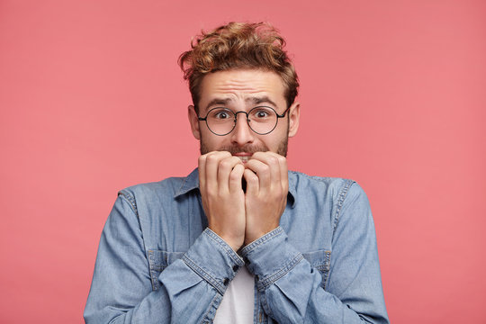 Worried hipster guy bites nails, looks nervous before passing exam or important event in his life. Embarrassed fashionable young man being afraid of difficulties, stands against pink background