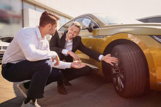 Salesman showing new car to customer outdoors