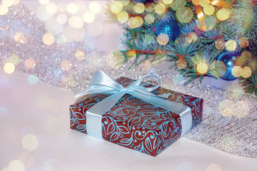 New Year background. Christmas composition. Christmas gift under the Christmas tree on a white background. Christmas presents. Blue toys on the Christmas tree and shiny decorations. Xmax. Noel. 2018