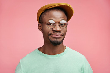 Delightful Afro American male wears trendy hat, smiles with full lips, has good mood after going shopping with wife, buys new round spectacles, isolated over pink background. People, ethnicity