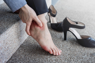 Health Care concept. Female Suffering from Pain in Ankle or Foot, Effect from Hard Walking or Comfortable Shoes, Barefoot Business Woman sitting at stair, High Heels as background