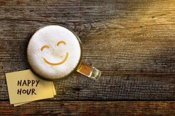 Happy Hour Concept for Bar, Cafe or Night club to Promote an Offer, Smiley Face on Foam in Glass of Beer over Wooden Table, Top View