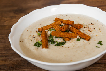 Mushroom cream soup with croutons, herbs and spices on a wooden background.