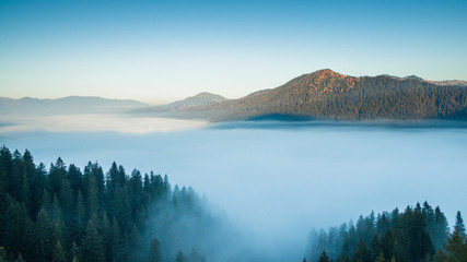 Aerial view of the morning fog between the mountains.. Aerial landscape fog over the plain between the peaks of the mountains