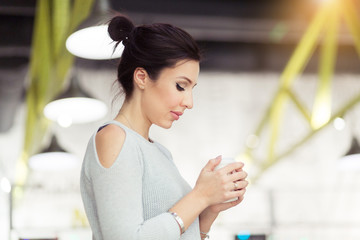 Portrait of happy brunette woman with mug in hands in coffee shop