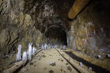 Underground abandoned ore mine shaft tunnel gallery with ice stalactites stalagmites