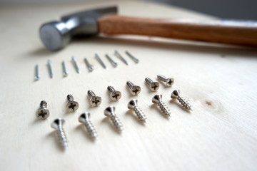 Nails, screws, and a hammer on home improvement construction site