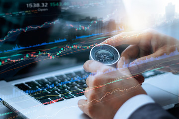 Businessman holding compass and data analyzing, using laptop stock market graph on screen, finance data and technology concept