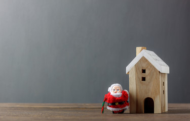 Santa Claus and white wooden home on modern rustic brown wood.Essential decorations & Ornaments of Merry Christmas in winter season concept.Several accessories decor festival.Free space for wording.
