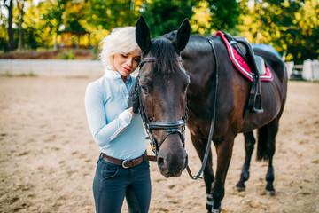 Female rider hugs her horse, horseback riding