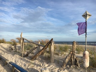 A purple flag blowing in the wind on the beach at Robert Moses State Park on Fire Island, NY