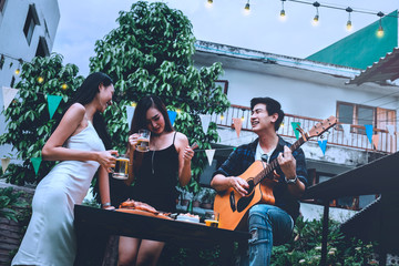 Group of young asian people happy while enjoying Night party and play guitar on garden home