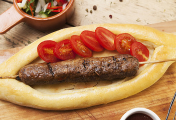 sausage grill with cherry tomatoes on a kitchen wooden table