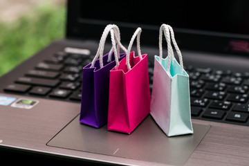 Three colorful paper shopping bags on laptop keyboard. Ideas about online shopping. e-commerce or electronic commerce is a transaction of buying or selling goods or services online over the internet.