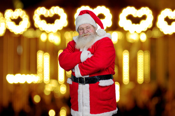 Santa Claus with crossed arms. Front view of old bearded Santa Claus standing with arms crossed on New Year light background. Photo of realistic Santa Claus in eyeglasess, blurred background.