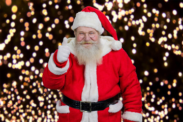 Happy Santa giving thumb up. Kind Santa Claus showing gesture ok on New Year lights. Realistic Santa Claus, portrait.