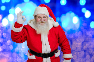 Happy Santa Claus showing ok sign. Smiling Santa Claus showing ok gesture standing on blue shiny background. Aged Santa Claus doing gesture.