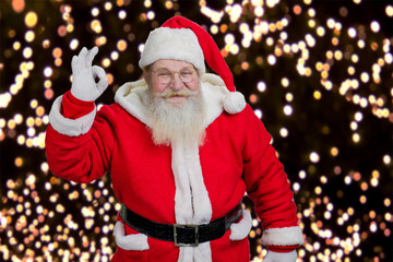 Santa showing ok gesture. Santa Claus showing hand okay sign on Ney Year lights background.