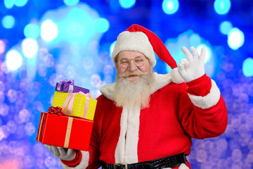 Santa Claus with Christmas gifts. Realistic Santa Claus holding boxes with presents and showing sign ok, blue shimmering background.
