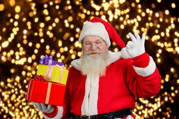 Happy Santa on New Year lights background. Smiling male Santa Claus holding pile of Christmas presents and showing okey sign. Santa Claus with gift boxes.