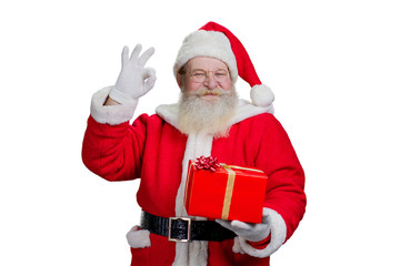 Happy Santa Claus on white background. Portrait of cheerful Santa Claus holding box with present and showing ok gesture. Festive mood and presents season.