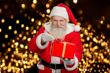 Happy Santa Claus offering present. Kind Santa Claus with red gift box on festive lights background.