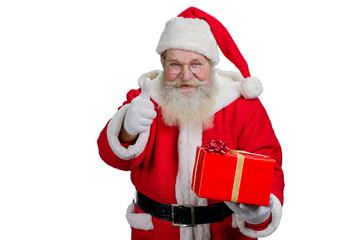 Portrait of Santa Claus with red gift box. Happy Santa Claus gesturing thumb up, isolated on white background. Studio shot of cheerful Santa with gift.