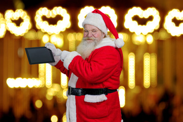 Santa Claus holding computer tablet. Senior santa Claus holding digital tablet and pointing on it with index finger on festive lights background. Santa Claus and gifts.