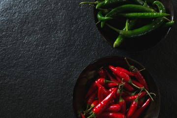 Green and red chili pepper in bowl